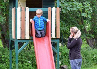 Spielturm mit Rutsche im großen Garten